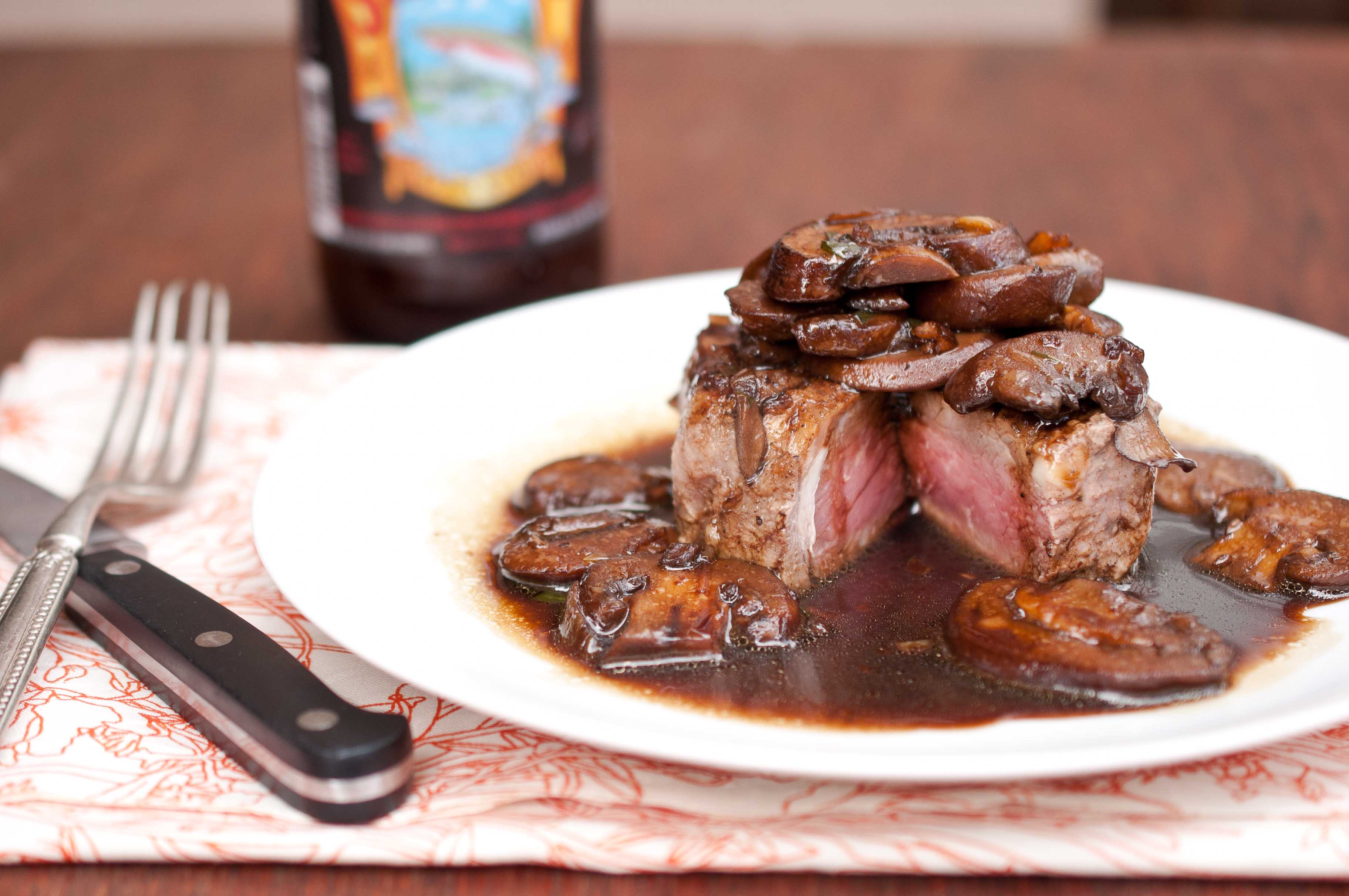 top each steak with mushroom sauce serve with stout beer